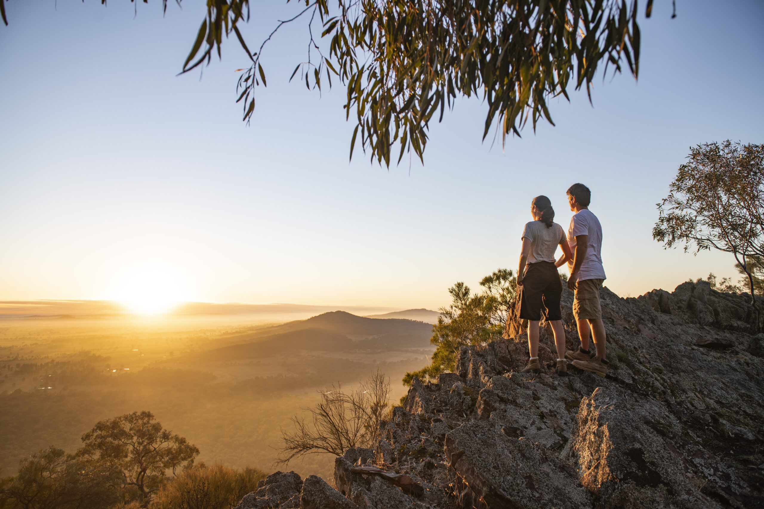 Two people watching the sunrise from a mountaintop